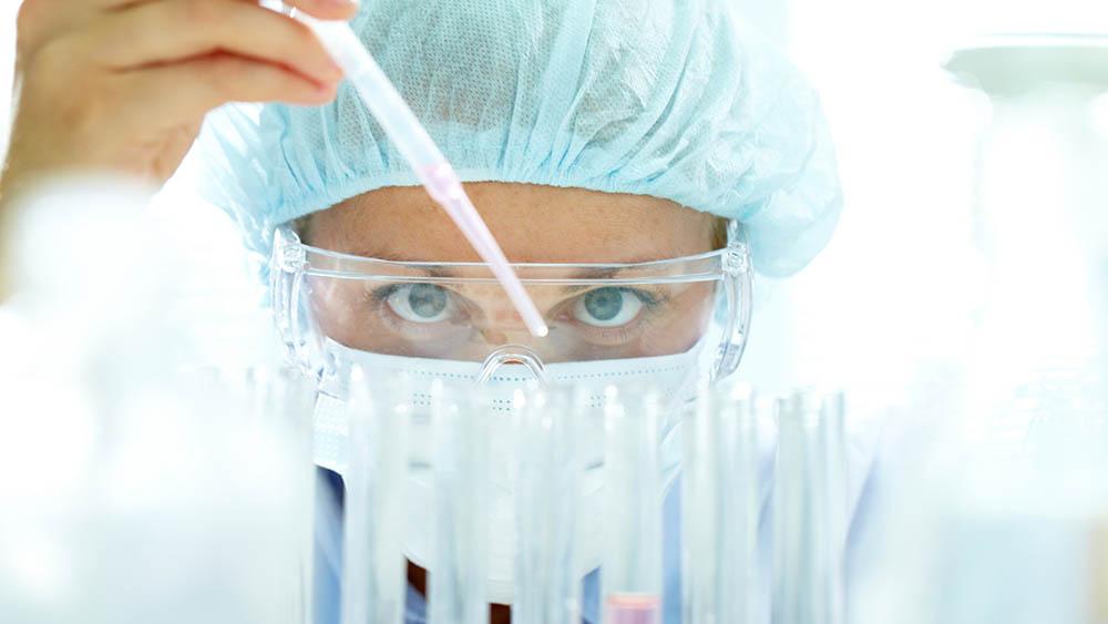 Cientista em laboratório trabalhando com tubos de ensaio.