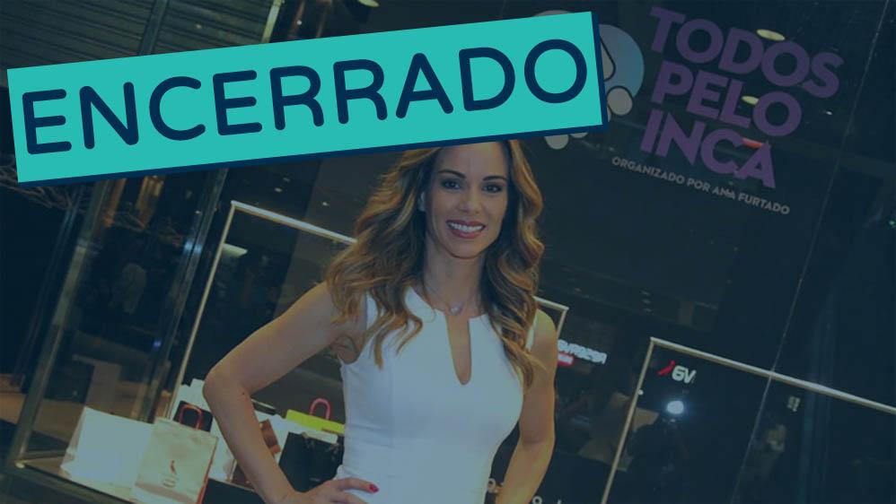 Ana Furtado em frente a vitrine adesivada com o logo da campanha Todos Pelo Inca encerrado.