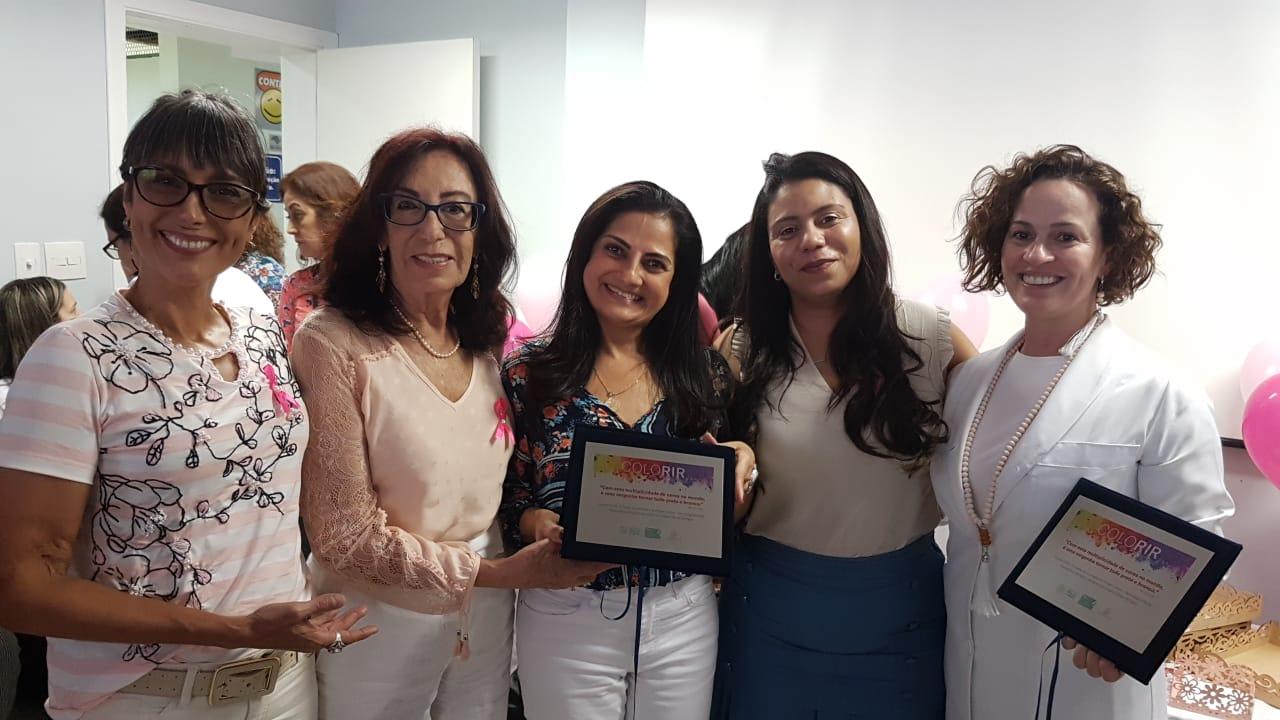 Mulheres do Projeto Colorir segurando placas celebrando o evento.