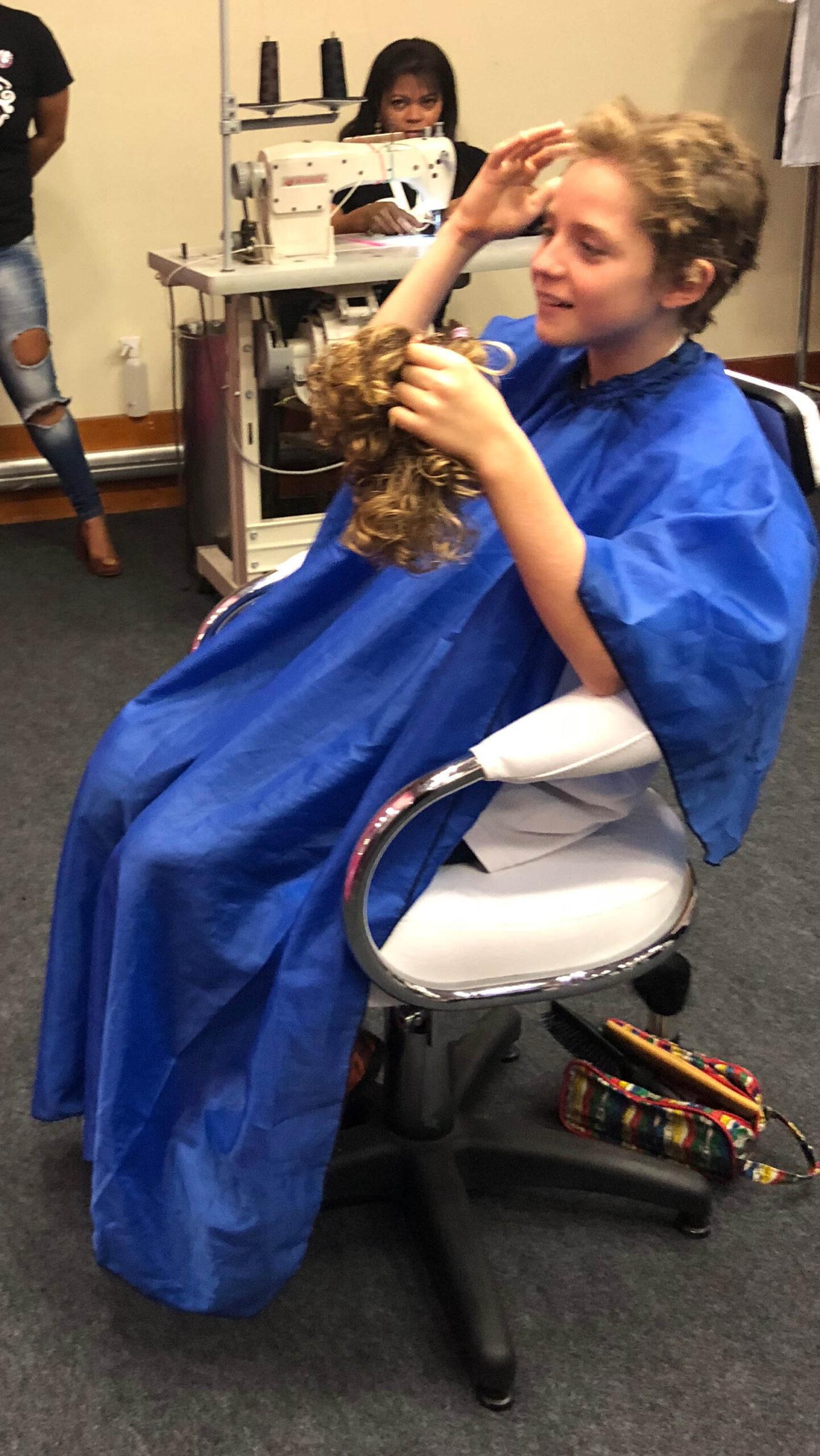 Menino alisando sua cabeça após doar cabelo para pacientes com câncer.