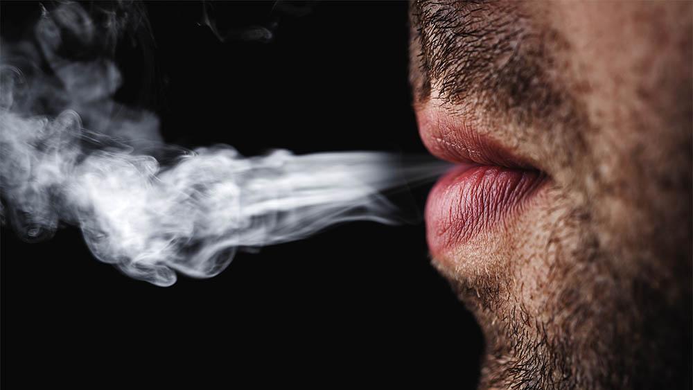 Close em uma boca de homem de perfil exalando fumaça de cigarro em um fundo preto.