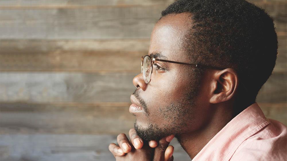 Rosto de homem negro pensativo de perfil.