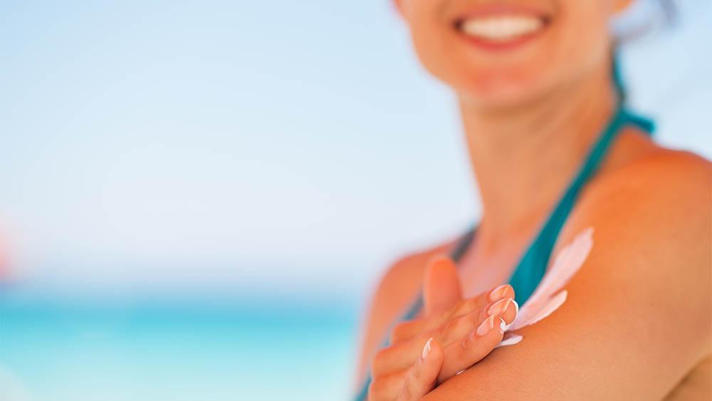 Close na mão de uma mulher passando protetor solar no próprio braço.
