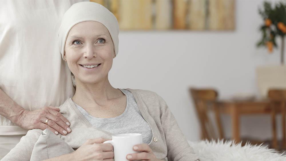 Mulher sorridente usando touca e com a mão de amiga em seu ombro.