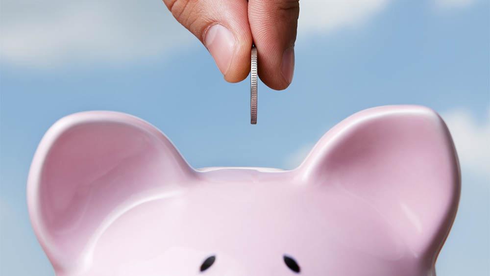 Dedos segurando uma moeda colocando em um cofrinho de porco.