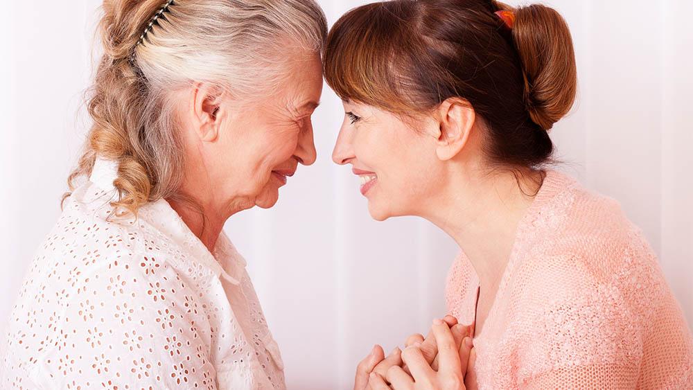 Mulher idosa à esquerda e mulher mais jovem à direita com a testa encostada uma na outra e sorrindo.
