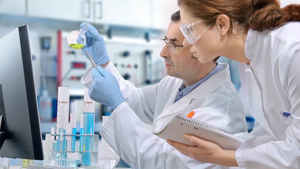 Perfil de um cientista segurando um recipiente de química e uma cientista observando ao seu lado.