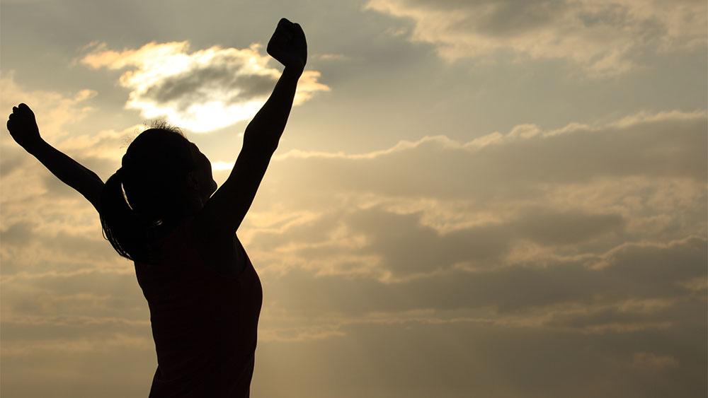 Silhueta de mulher com os braços levantando em uma paisagem de entardecer.