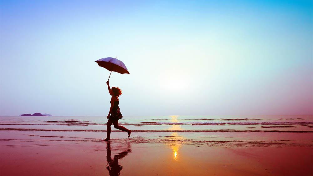 Mulher correndo na praia segurando guarda-chuva.