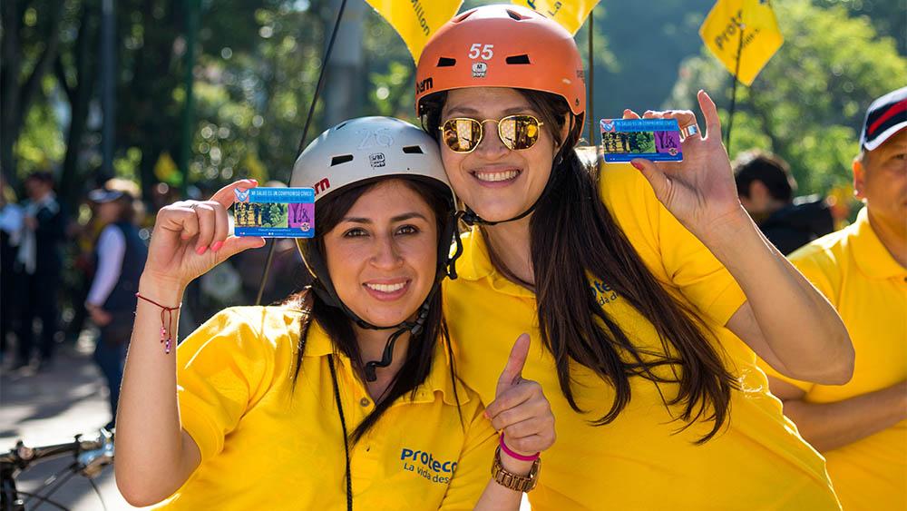 Duas participantes da campanha do Dia Mundial do Câncer mostrando suas carteirinhas da Liga Colombiana Contra o Câncer.
