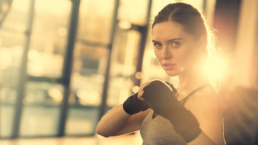 Mulher com luvas de luta em posição de guarda olhando para a câmera.
