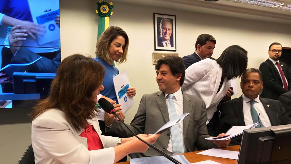Representante do IVOC entregando documento sobre a campanha #simparaquimiooral ao ministra da Saúde Henrique Mandetta.