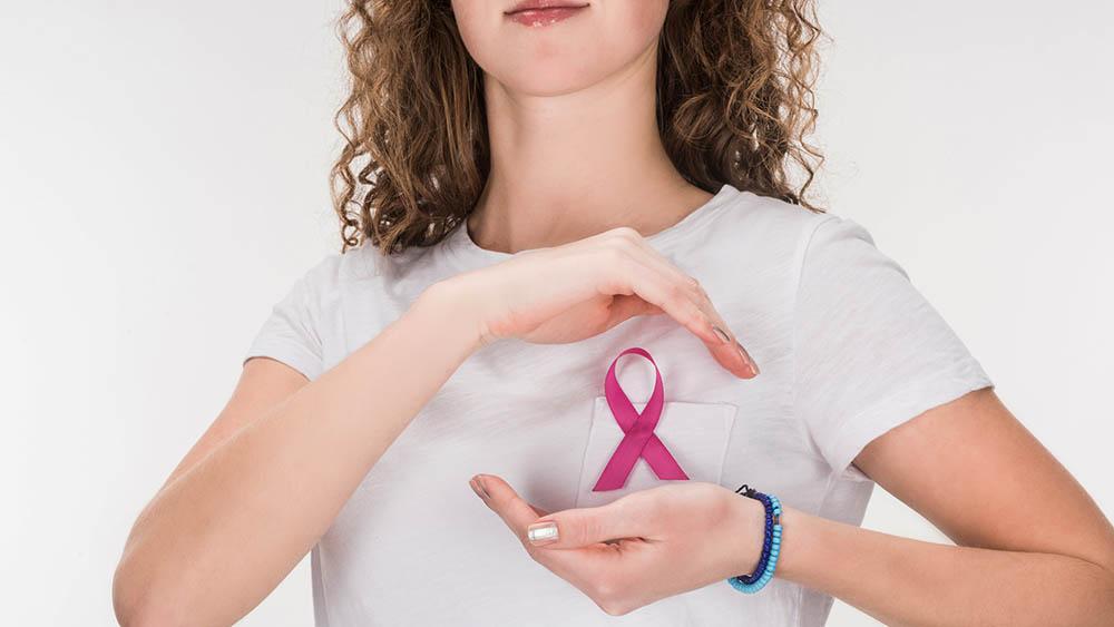 Mulher com laço rosa na lapela fazendo gesto de proteção com as duas mãos sobre a região.
