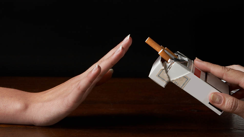 """Mão sinalizando """"não"""" para outra mão que oferece uma caixa de cigarros."""