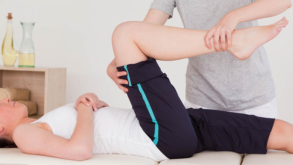 Fisioterapeuta manuseando perna direita de paciente deitada em cama.