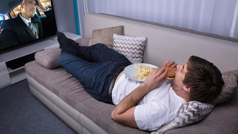 Homem jovem deitado em sofá comendo hambúrguer e assistindo a televisão.