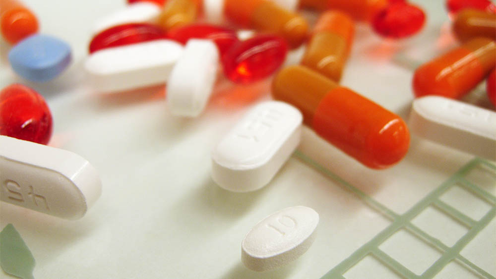 Comprimidos e cápsulas de medicamento espalhadas em superfície.